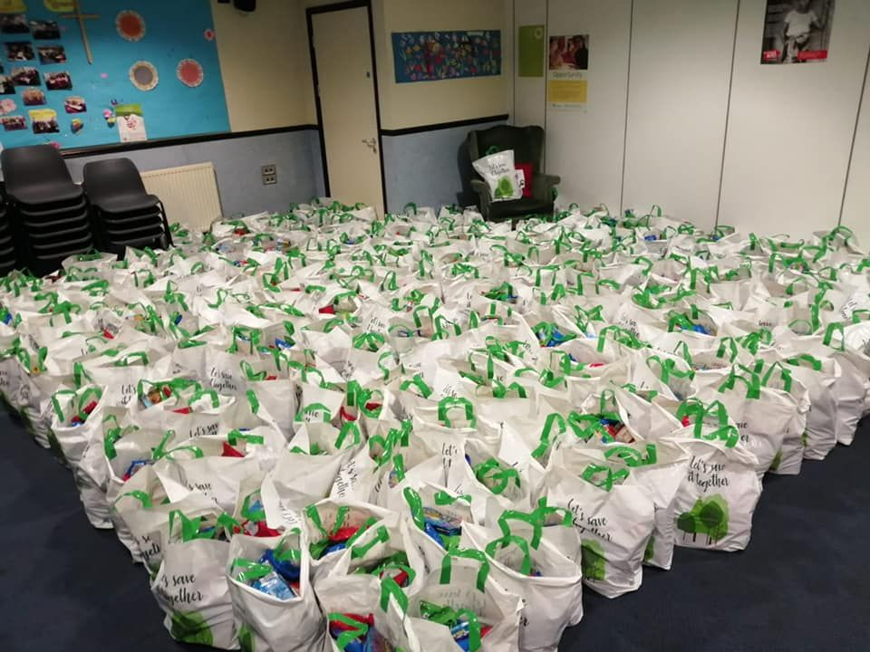 a room almost full of bags packed with food ready to be delivered by volunteers