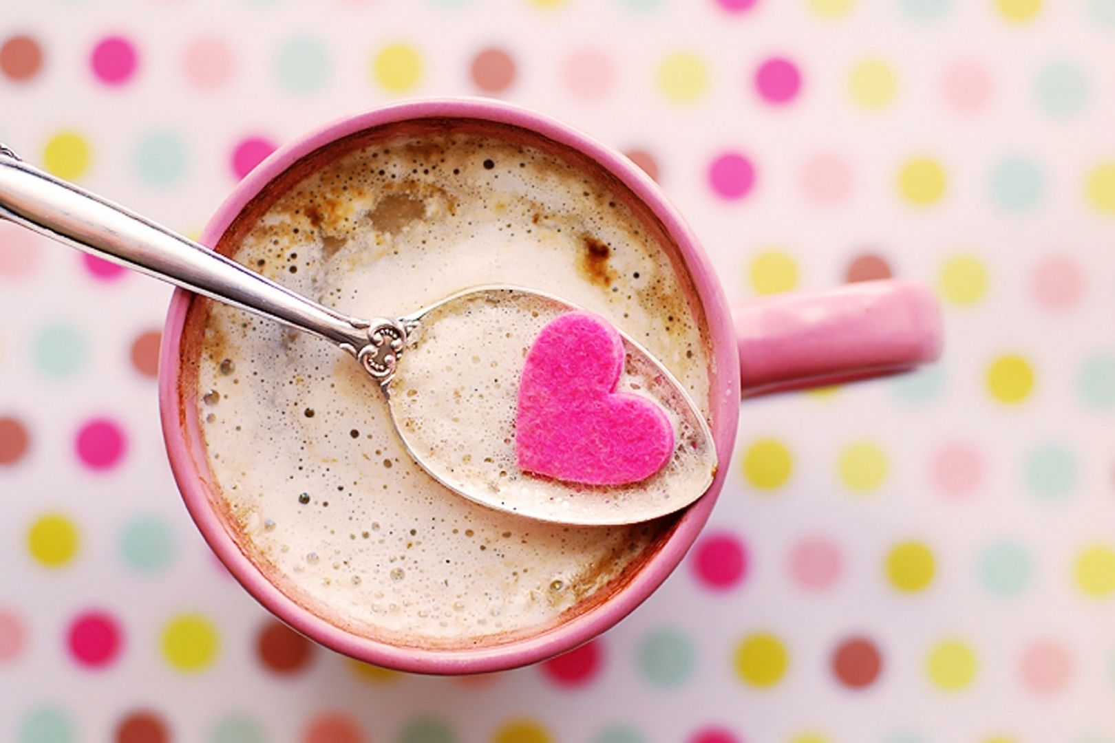 cup of coffee with teaspoon holding pink heart