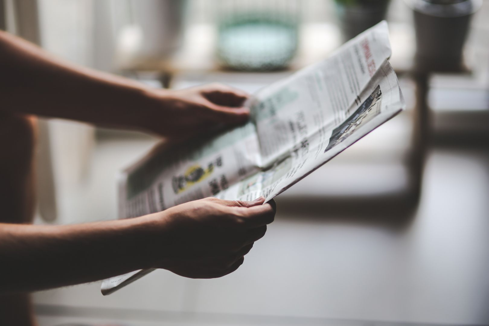 a newspaper held by pair of hands