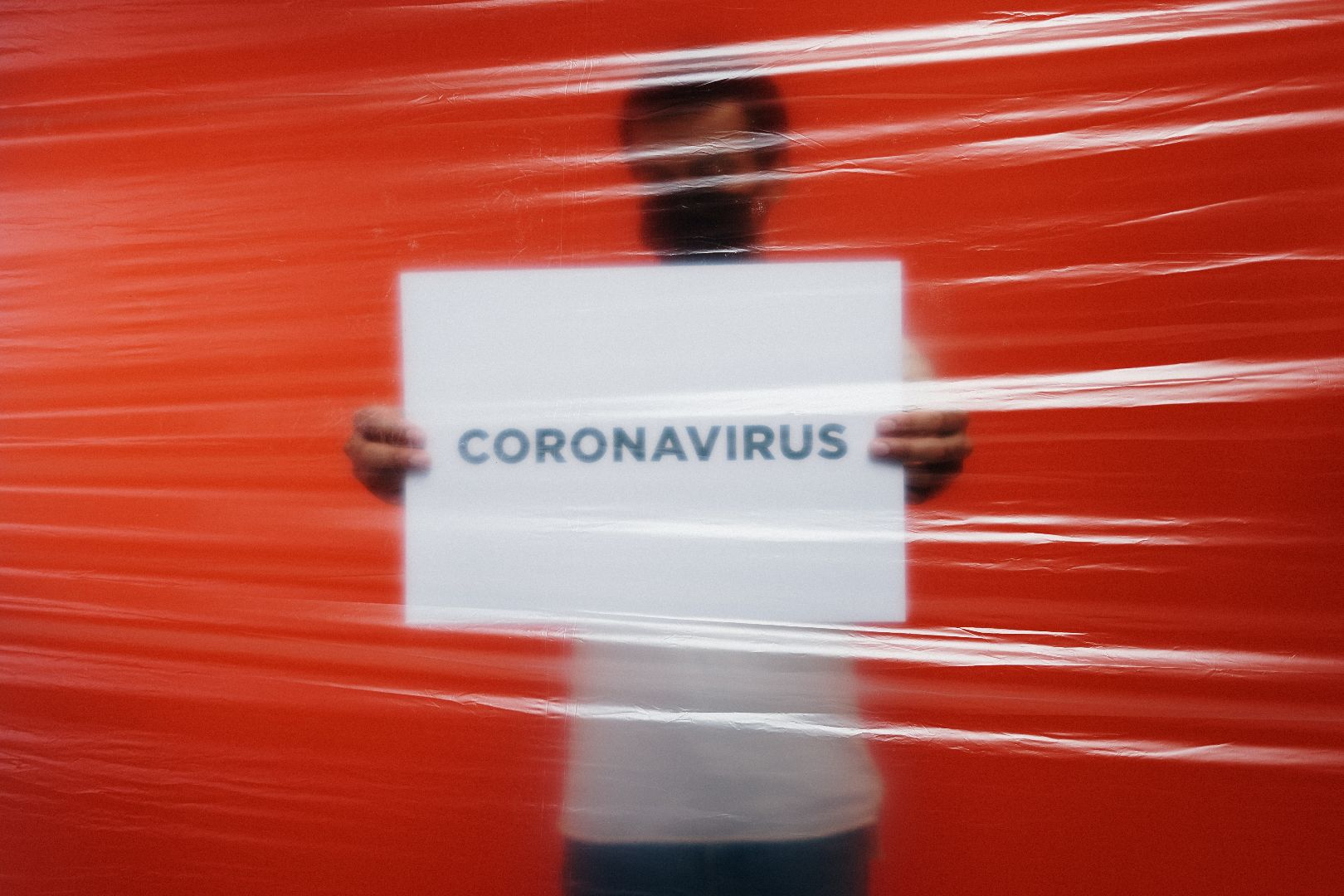 Photo of male holding white sign with 'coronavirus' printed across